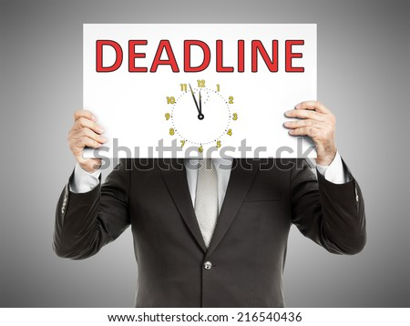 A business man holding a paper in front of his face with the text deadline - stock photo