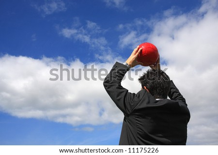 A business man holding a red soccer ball - stock photo