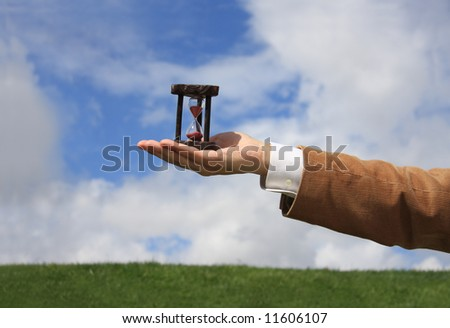 A business man holding a wooden hourglass - stock photo