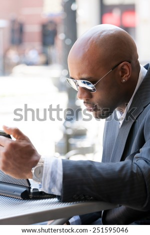A business man in his early 30s working on his laptop or netbook computer outdoors. - stock photo