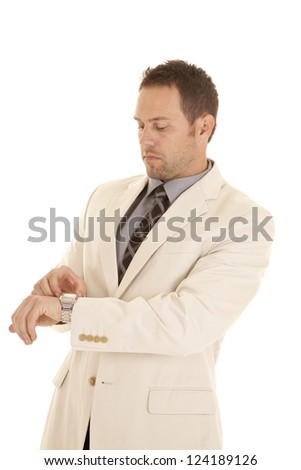 A business man in his suit looking down at his watch with a serious expression. - stock photo