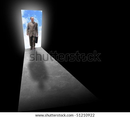 A business man is holding a briefcase and standing at an open door with light behind him. The room is dark and black. Can represent opportunity, fear, risk or success. - stock photo