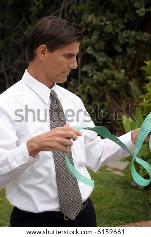 """a business man is overwhelmed by a roll of """"Keep this coupon"""" coupons Representing """"red tape"""", business, buracity, etc - stock photo"""