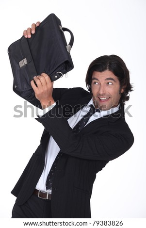a business man is protecting his face with a briefcase, he looks amused - stock photo