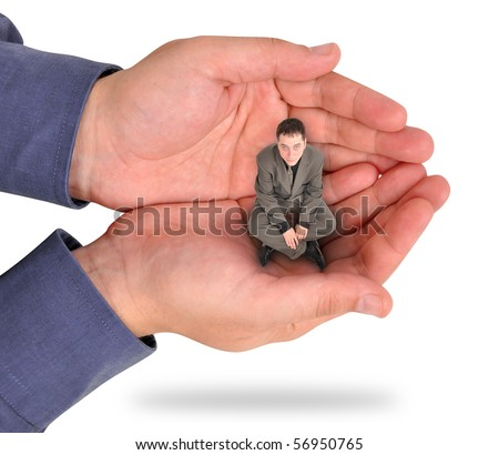 A business man is sitting in the palm of his bosses hand on a white background. He looks unhappy and feels trapped and weak at his job. Use it for a strength or struggle concept. - stock photo