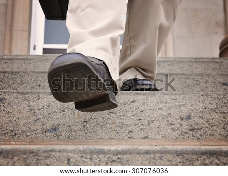 A business man is stepping down the stairs at an office for a power, challenge or motivation concept. - stock photo