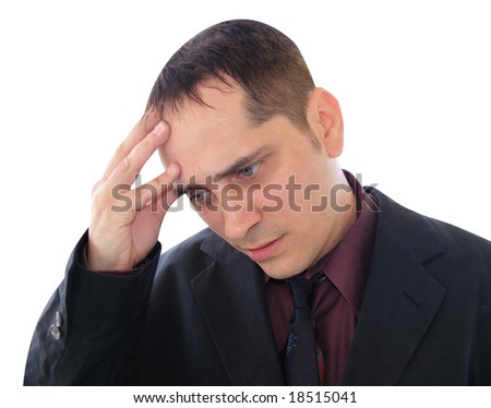 A business man is stressed out and is holding his hand to his forehead. - stock photo