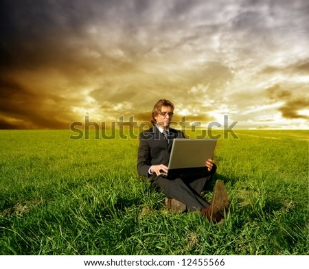 a business man on a grass field with a laptop - stock photo