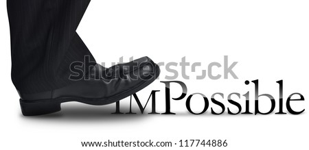 A business man's foot is stepping on the work impossible to make the work possible. There is a white background. use it for a motivational concept. - stock photo