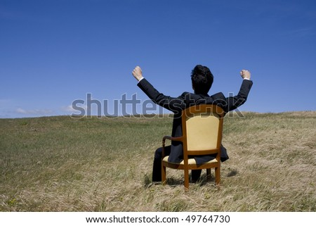 A business man sit on an armchair on the middle of a green field - stock photo