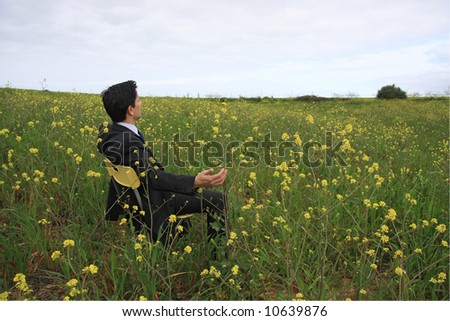 A business man sitting in a field enjoying the nature - stock photo