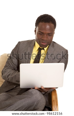A business man sitting in his chair working on his laptop with a small smile on his face. - stock photo