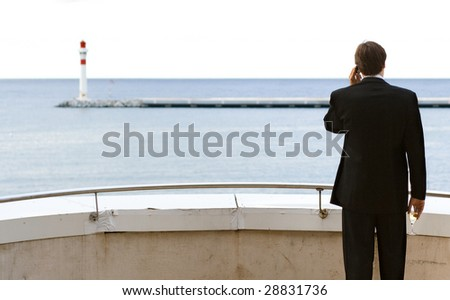 A business man standing on a balcony and talking on the mobile phone with a glass of champagne in his hand while looking at the sea with a lighthouse on the horizon - stock photo