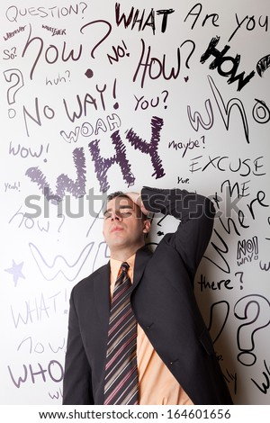 A business man that looks worried about questions floating around in his head. - stock photo