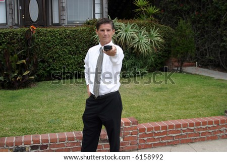 a business man uses a universal remote controll outside to controll TV, the Weather, people under hypnosis, and YOU! - stock photo