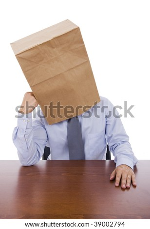 A business man with a cardboard bag on his head with a pensive expression - stock photo