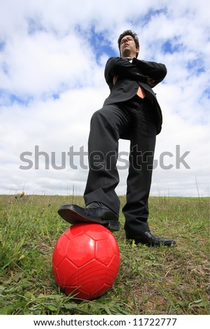 A business man with a red ball on a field - stock photo