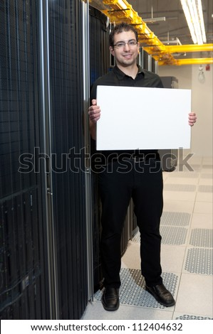 A business man with a satisfied look holding a white board in a datacenter.
