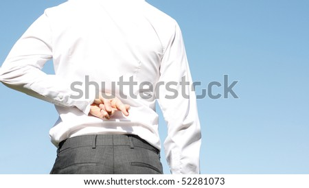 A business man with fingers crossed - stock photo