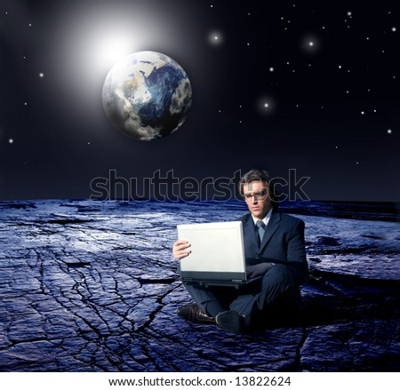 a business man with laptop and a earth space view - stock photo
