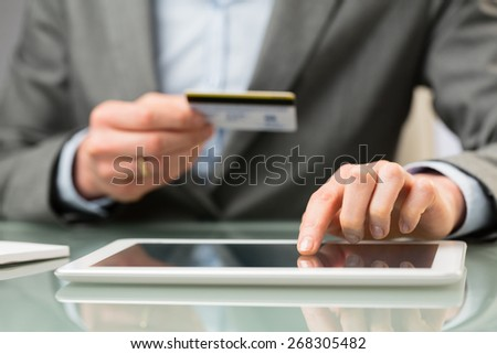 A business person enters credit card information on a tablet computer. Closeup image. - stock photo