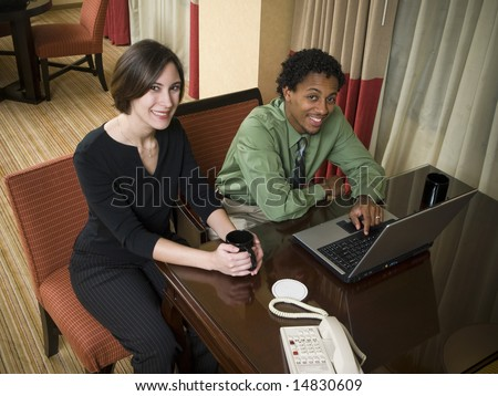 A business team looks at the camera while reviewing good results on their laptop computer in a hotel room during a business trip.