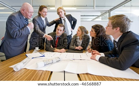 A business team of architect and their senior manager discussing blue prints