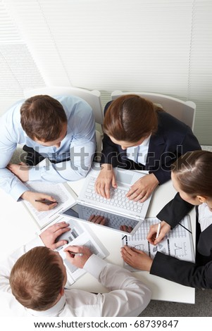 A business team of four sitting at one table and working - stock photo