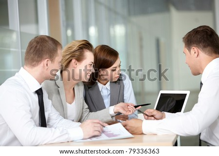 A business team of four sitting at table and planning work - stock photo