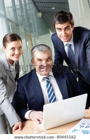 A business team of three looking at camera at workplace - stock photo