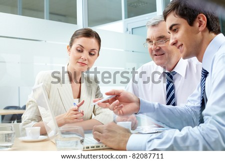 A business team of three sitting in office and planning work - stock photo