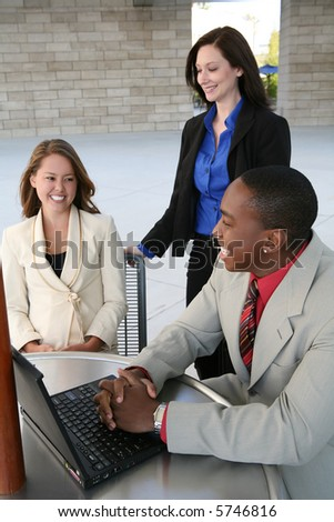 A business team of two women and a man at a table (Focus on Man)