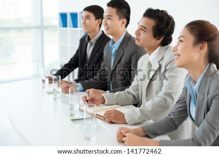 A business team sitting at the conference in a line inside