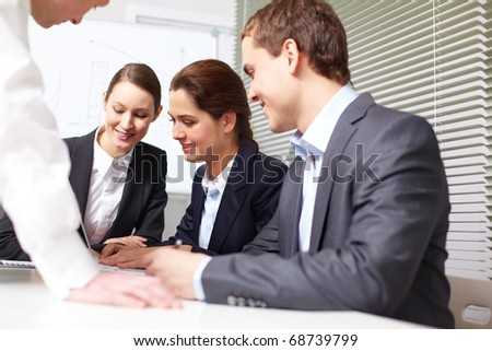 A business team sitting in the office and sharing ideas - stock photo
