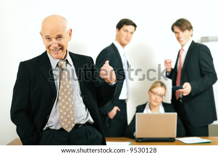 A business team with a portrait of the very confident team leader in foreground (selective focus only on the team leader!) - stock photo