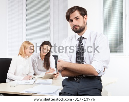 A business team with boss in front looking at camera - stock photo