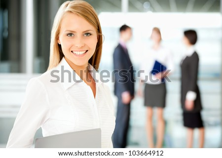 A business team with pretty business woman in front looking at camera - stock photo