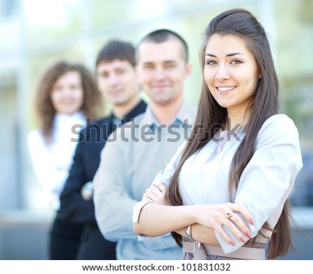 A business team with pretty leader in front looking at camera and smiling - stock photo