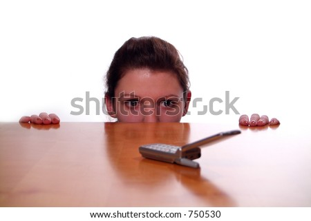A business woman hiding behind a desk. - stock photo