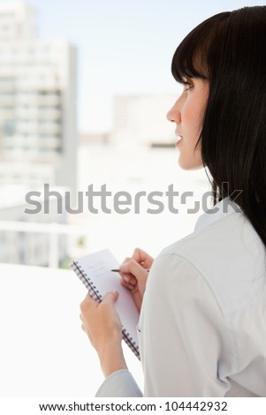 A business woman looks upwards as she stops writing on the notepad in her hand - stock photo