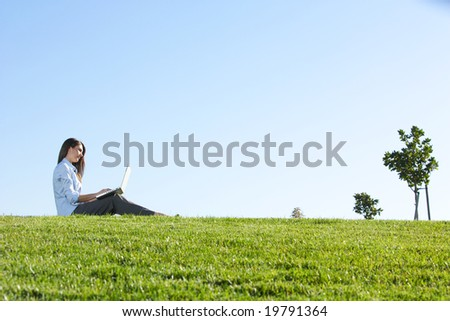A business woman on a laptop in a field out side the office - stock photo