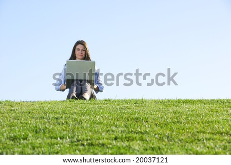 A business woman on a laptop in a field out side the office