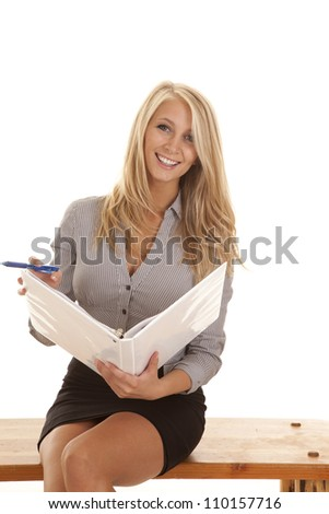 A business woman sitting on a bench holding her folder with a smile on her face. - stock photo