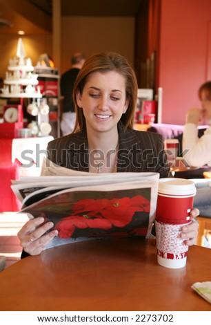 A business woman taking a coffee break and reading the newspaper