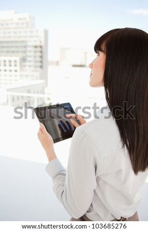 A business woman uses a tablet pc in her office as she looks up - stock photo
