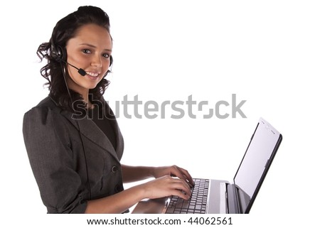 A business woman working on her computer with her headset on her head.