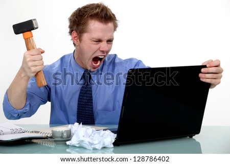 A businessman about to smash his laptop with a hammer.