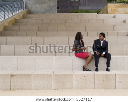 A businessman and businesswoman having a discussion while sitting in front of a modern building