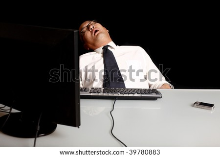 A businessman asleep at his desk.