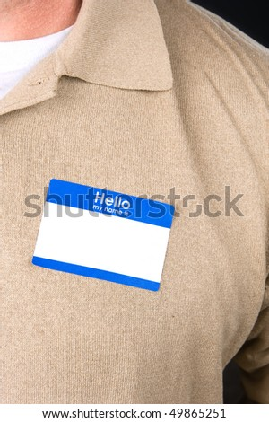 A businessman at a tradeshow wears a blank name tag. - stock photo